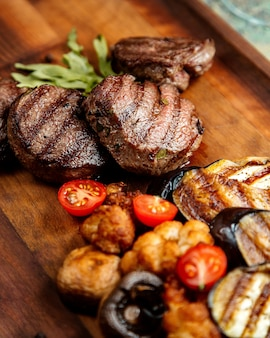 Grilled meat cutlet with eggplant mushroom tomatoes and rosemary on board