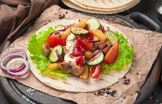 Мясо на гриле, картофель-фри, свежие овощи и соусы на коричневой стене. приготовление тако, шаурмы, буррито. крупный план, вид сбоку.