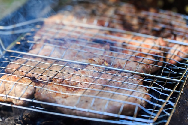 炎と石炭でバーベキューの肉のグリル