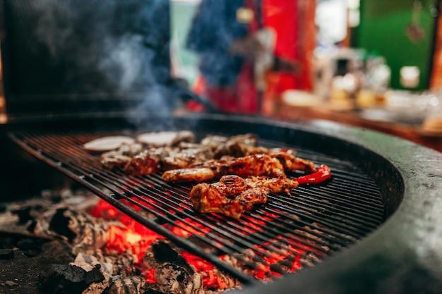 Мясо на гриле в барбекю с огнем и углями