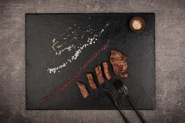 검은 돌 접시에 구운 고기를 놓고 칼 옆에 소금 후추 통