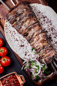Grilled meat on lavash bread with onion salad and herbs.
