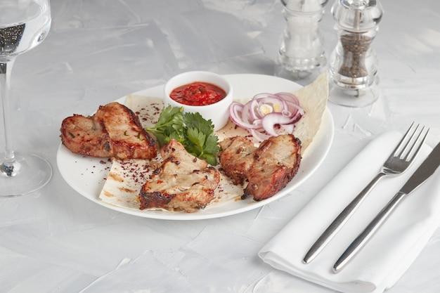 皿に焼いた肉、レストランで提供、明るい背景