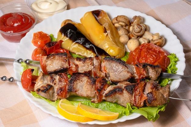 Мясо на гриле на листьях салата и запеченные овощи на белой тарелке
