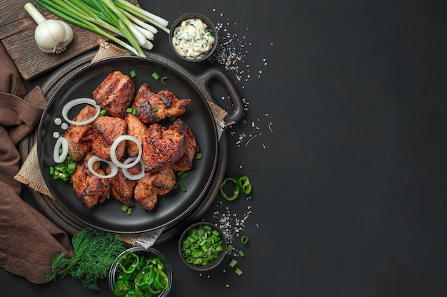 복사할 공간이 있는 어두운 배경에 신선한 허브와 양파와 함께 불에 구운 고기. 평면도. 케밥, 바베큐.