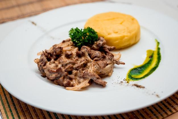 하얀 접시에 구운 된 고기입니다. 레스토랑.