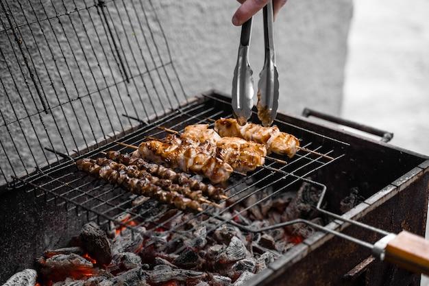 숯불에 금속 그릴에 나무 꼬치에 구운 고기. 치킨, 하트 요리.