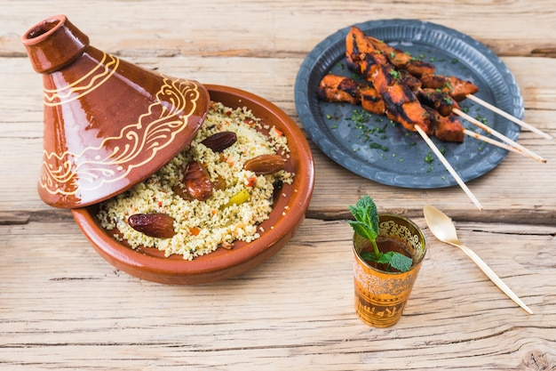 Grilled meat and quinoa salad with dried plums near cup