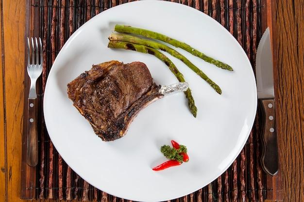 Жареные мясные ребрышки на белой тарелке с помидорами, чесноком и темным острым соусом на борту