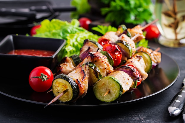 Grilled meat skewers, chicken shish kebab with zucchini, tomatoes and red onions