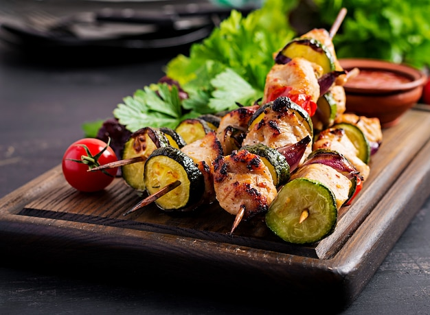Grilled meat skewers, chicken  shish kebab with zucchini, tomatoes and red onions.