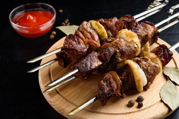 Шашлык из мяса на гриле, шашлык с кетчупом и специями на черном фоне.