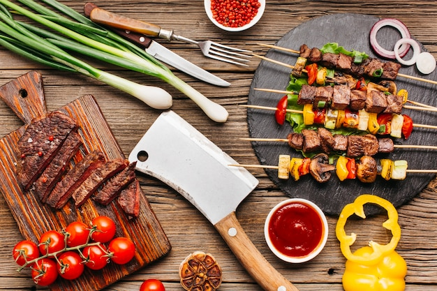 Grilled meat skewers and steak with vegetable on wooden desk