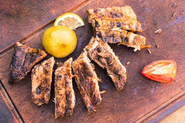 Grilled meat and sliced ​​lemon tomato  on table