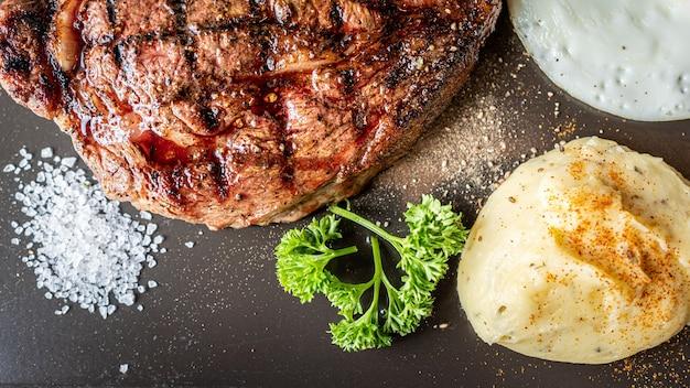 Мясной стейк на гриле и картофельное пюре с солью на темной поверхности