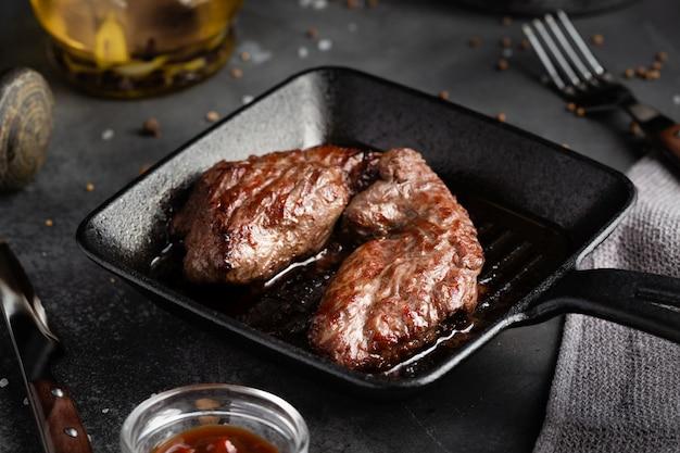 Grilled meat steak machete with salt and pepper on slate board black