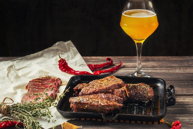 Grilled meat steaks on frying pan and glass of beer on a dark wooden background