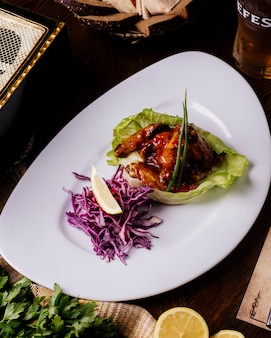 Grilled meat in teriyaki sauce in lettuce leaf with red cabbage salad and lemon.