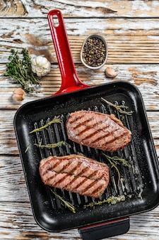 Grilled meat top blade steaks in a frying pan