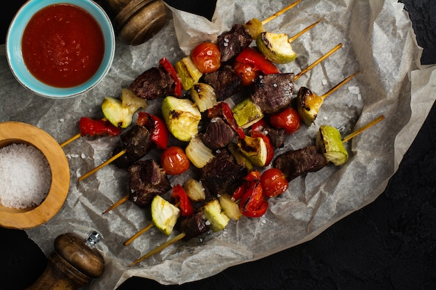 Grilled meat and vegetables cabobs over black stone table