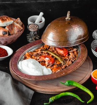 Grilled meat and vegetables with yogurt in a pan.