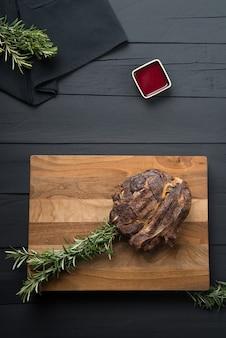 Мясо на гриле с зеленью и соусом на разделочной доске на черном деревянном фоне