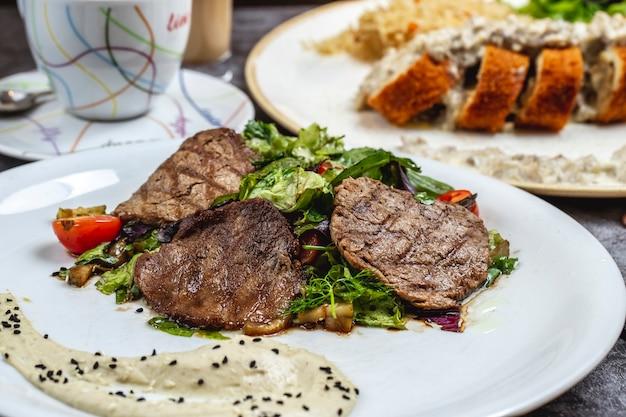 Мясо на гриле с листьями салата грибы томатный хумус