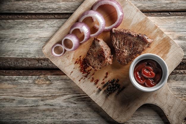 Мясо на гриле со специями и томатным соусом на изношенных деревянных фоне