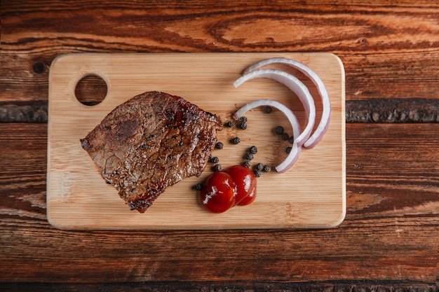 Grilled meat with spices and tomato sauce on a worn wooden background