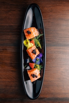 Grilled medium rare salmon cube topping with caviar and served with strawberry and orange in black plate.
