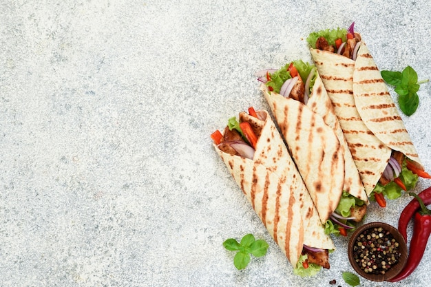 Grilled mexican tortilla with vegetables on a concrete background. view from above.
