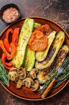 Овощи на гриле в деревенской тарелке. темный фон. вид сверху.