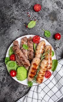 Жареные колбаски из мюнхенской телятины и мясные рулеты, завернутые в бекон, чевапчичи или кебаб кофта. кетогенная диета, вертикальное изображение. вид сверху. место для текста.