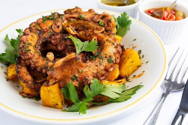 Жареный осьминог и картофель над белой тарелкой в испанском ресторане.