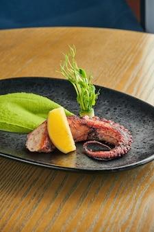 タコの触手焼き、木製の壁に黒い皿に緑のスムージーとスパイシーソース。クローズアップ、セレクティブフォーカス