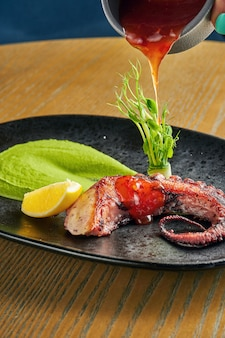 Grilled octopus tentacle with green smoothie and spicy sauce on a black plate on a wooden wall. close up, selective focus