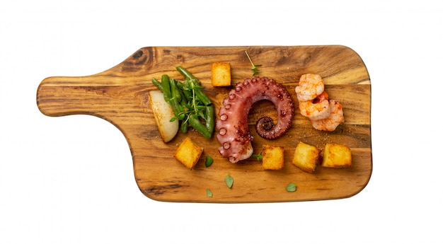 Grilled octopus tentacle on a wooden cut board served with shrimps