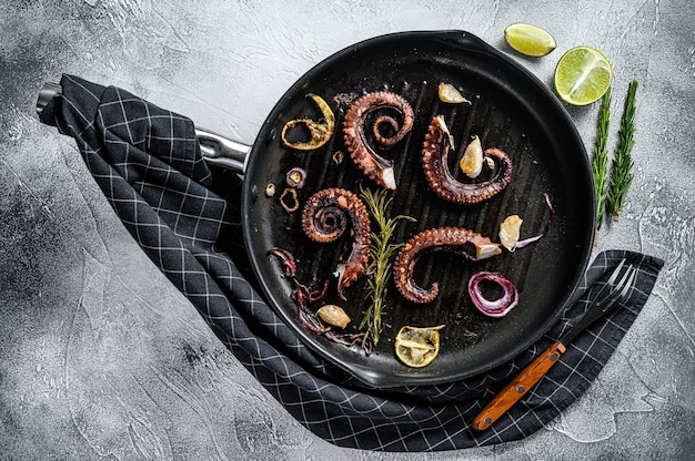 Grilled octopus tentacles with rosemary, garlic and butter in a pan