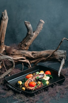 Grilled octopus with tomatoes olives and herbs on an elegant background with a tree
