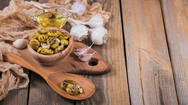 Жареные оливки с чесноком, оливковым маслом и специями на деревенском деревянном фоне