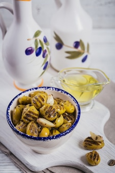 Grilled olives with garlic, olive oil and spices on white rustic wooden background