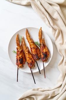 Куриные крылышки на гриле или барбекю, шашлык на тарелке