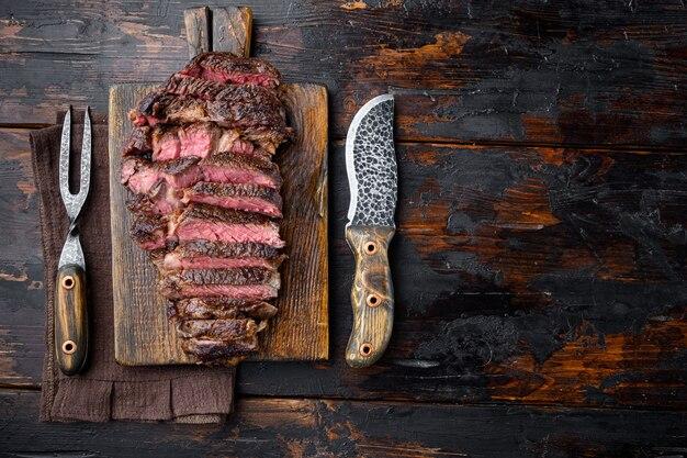 Набор рибай, приготовленный на гриле или жареный и нарезанный ломтиками из мраморного мяса, на деревянной сервировочной доске, с ножом и вилкой для мяса, на старом темном деревянном столе