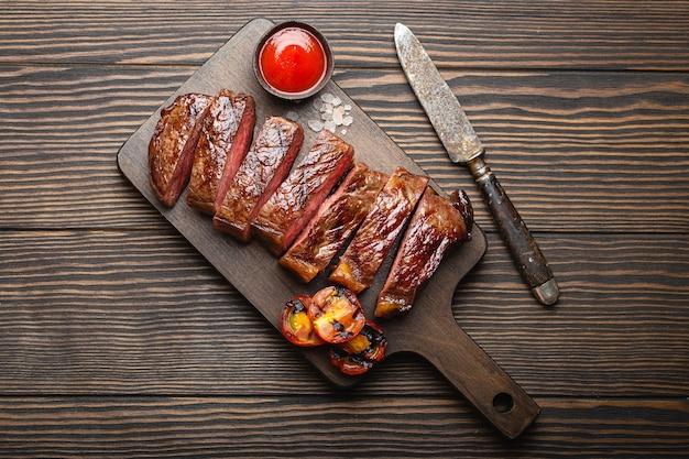 Жареный или жареный и нарезанный стейк из мраморного мяса, помидоры в качестве гарнира и соус на деревянной разделочной доске, вид сверху, крупный план, деревянный деревенский фон. концепция филе стейка из говядины