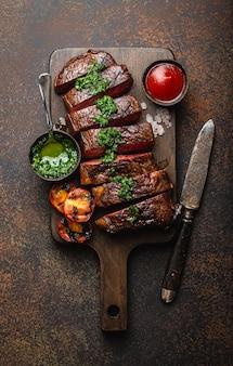 霜降り肉のグリルまたは揚げ物とスライスしたステーキ、フォーク、トマト、サイドディッシュ、木製のまな板にさまざまなソース、上面図、クローズアップ、石の素朴な背景。ビーフミートステーキのコンセプト