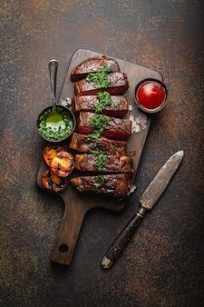 Жареный или жареный и нарезанный стейк из мраморного мяса с вилкой, помидорами в качестве гарнира и различными соусами на деревянной разделочной доске, вид сверху, крупный план, каменный деревенский фон. концепция стейка из говядины