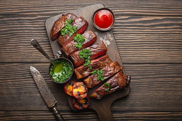 Жареный или жареный и нарезанный стейк из мраморного мяса с вилкой, помидорами в качестве гарнира и различными соусами на деревянной разделочной доске, вид сверху, крупный план, деревянный деревенский фон. концепция стейка из говядины
