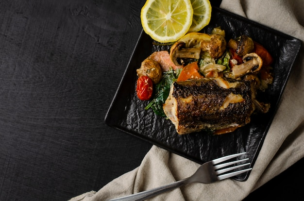 Grilled or oven baked hake fish on black plate.