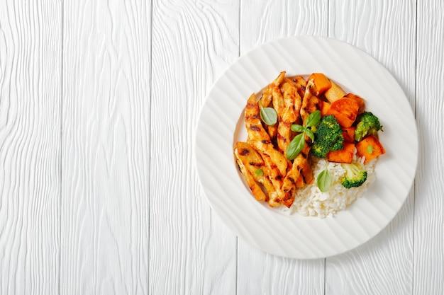焼き芋ご飯とブロッコリーを添えたパプリカチキンのグリルストリップを木製のテーブルの白いプレートに載せて、上から見た自由空間の水平方向のビュー