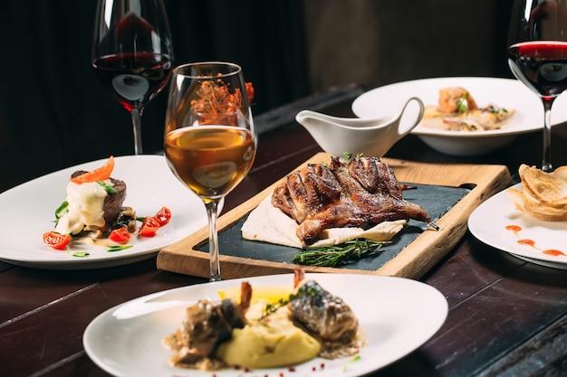 Жареная куропатка, сибас, тартар. разные блюда на столе в ресторане.